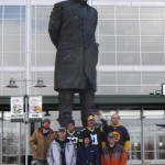 "League members of ""Twelve & Counting"" proudly hoist their trophies under the Vince Lombardi statue at Lambeau Field."